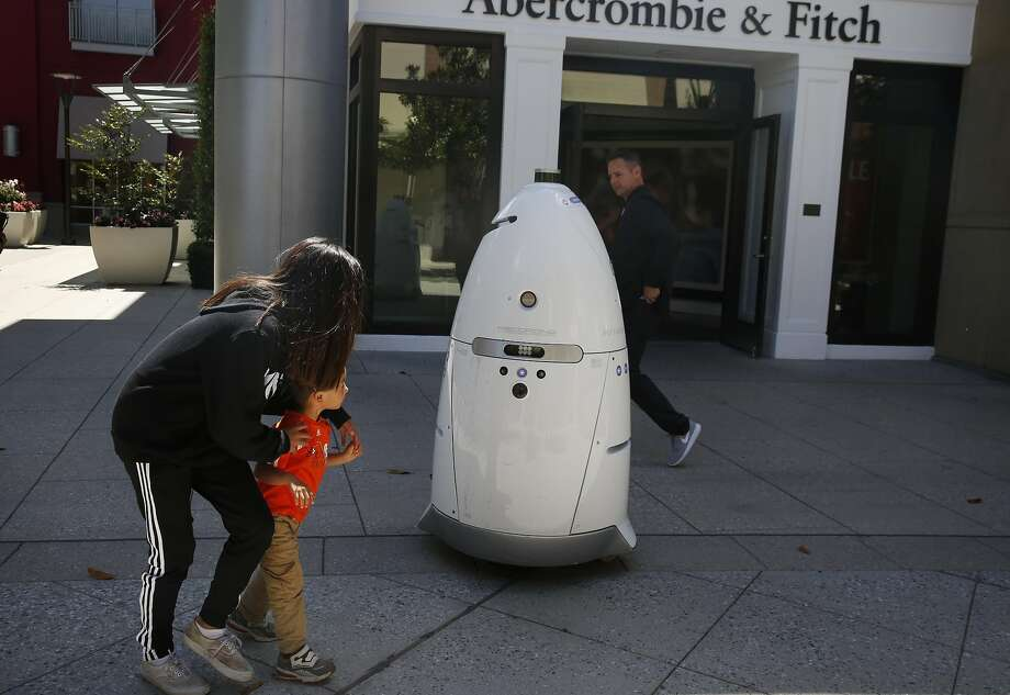 Hannah Stulbarg guides her cousin Zach Hensersky past a Knightscope K5 autonomous security robot at the Stanford Shopping Center in Palo Alto. Photo: Leah Millis, The Chronicle