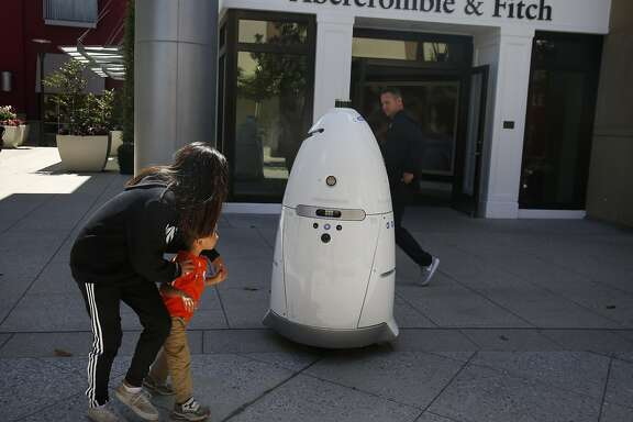 Hannah Stulbarg, 12, guides her cousin Zach Hensersky, 3, past a Knightscope K5 autonomous security robot as it roams around the Stanford Shopping Center June 15, 2016 in Palo Alto, Calif.
