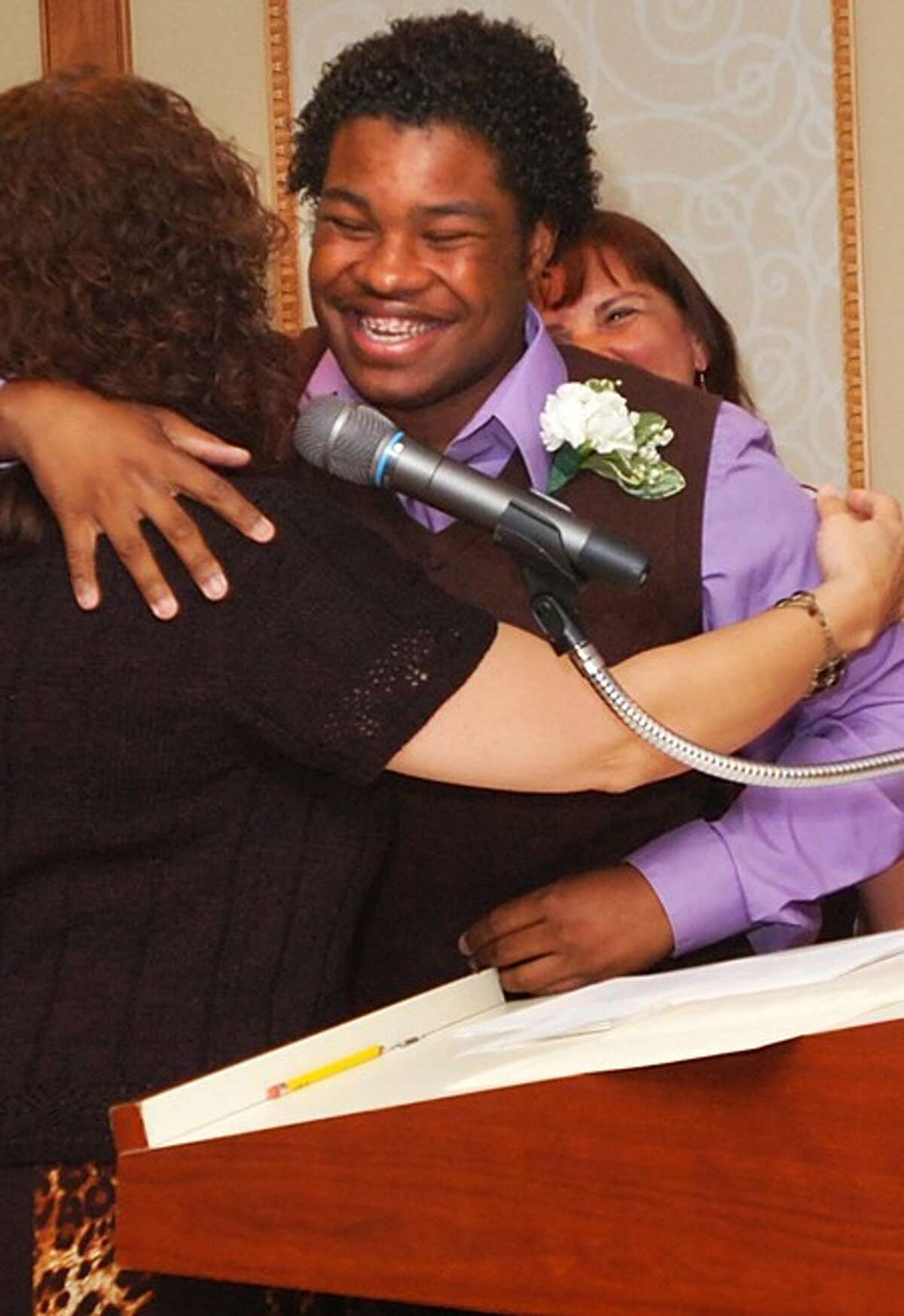 School to Career graduate Travis White receives congratulations from Denise Evon and Lisa Riieccio of the Norwalk Public Schools during the Graduation and Mentor Appreciation reception at the Norwalk Inn Thursday evening. Hour photo / Erik Trautmann
