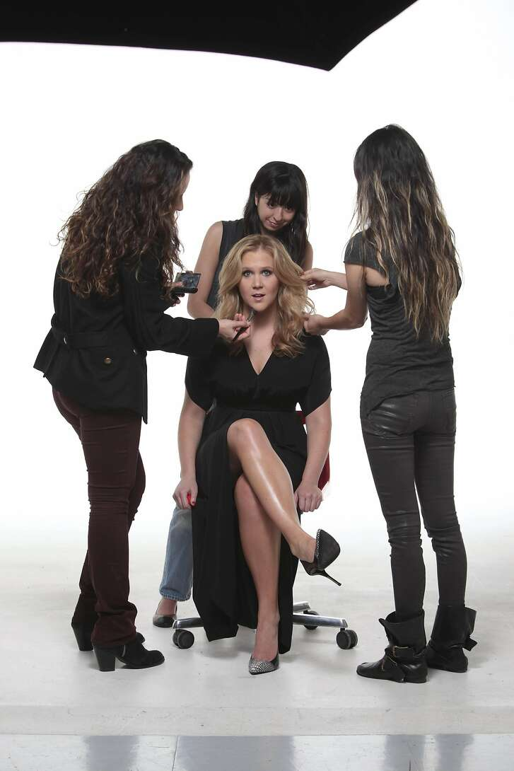 Amy Schumer, center, is styled by from left: makeup artist Fabiola Arancibia, stylist Danielle Nachmani and hair stylist Miok Donnelly in New York, April 11, 2013. The new Comedy Central show that spins around Schumer is as much the work of its staff as of its central player, as a six-month observation of the process reveals. (Tony Cenicola/The New York Times) -- PHOTO MOVED IN ADVANCE AND NOT FOR USE - ONLINE OR IN PRINT - BEFORE APRIL 21, 2013.