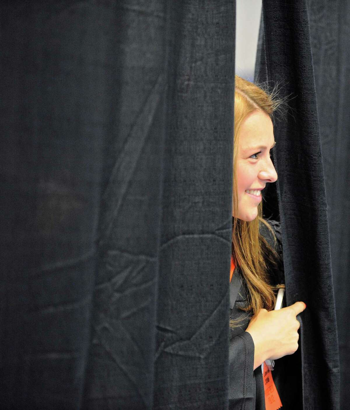 Kimberly Fessenden Weinstock peeks through a curtain looking for her parents as she waits for the Ridgefield High School 2016 Commencement Exercise to begin, Friday, June 17, 2016, at the O'Neill Center, Western Connecticut State University, Danbury, Conn.