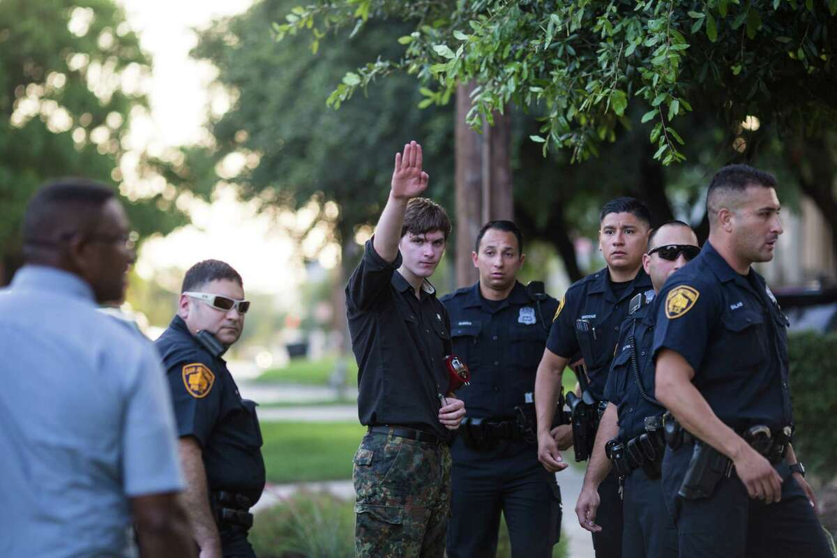 """Steven Billingsley, who arrived at Crockett Park with a sign bearing a homophobic slur and symbols of the Nazi party, does a """"Sieg Heil"""" salute as he talks with police after a scuffle with a man attending a vigil on Thursday, June 16, 2016, to honor the 49 victims killed in the recent mass shooting in Orlando."""