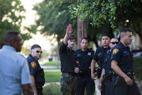 "Steven Billingsley, who arrived at Crockett Park with a sign bearing a homophobic slur and symbols of the Nazi party, does a ""Sieg Heil"" salute as he talks with police after a scuffle with a man attending a vigil on Thursday, June 16, 2016, to honor the 49 victims killed in the recent mass shooting in Orlando."
