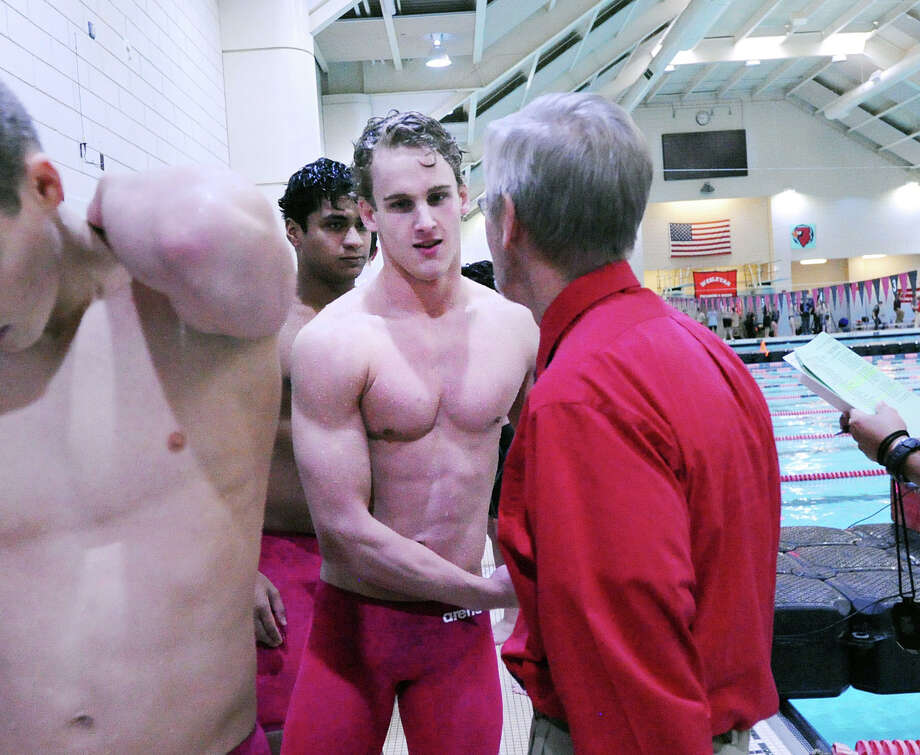 Jack Montesi of Greenwich, center, is congratulated by Greenwich coach Terry Lowe, right, after the Greenwich team took the 200 medley relay event during the CIAC boys class LL swimming championships at Wesleyan University, Middletown, Conn., Wednesday, March 16, 2016. Photo: Bob Luckey Jr. / Hearst Connecticut Media / Greenwich Time