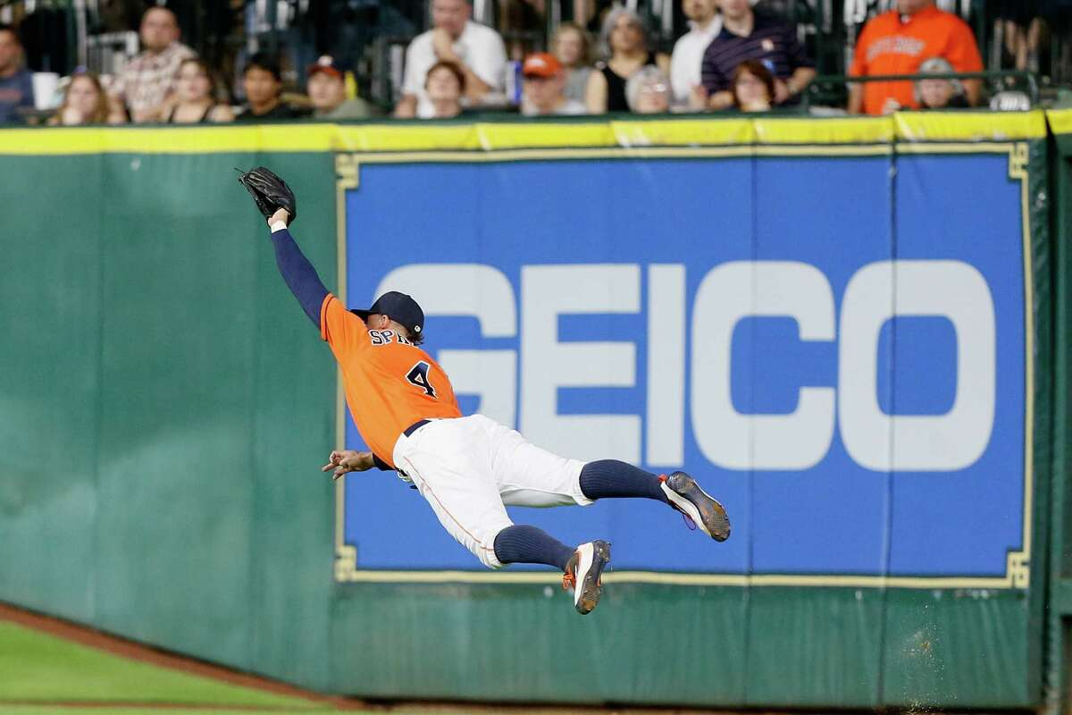 HOUSTON, TX - JUNE 17: George Springer #4 of the Houston Astros makes a diving catch on line drive by Adam Duvall #23 of the Cincinnati Reds in the sixth inning at Minute Maid Park on June 17, 2016 in Houston, Texas.