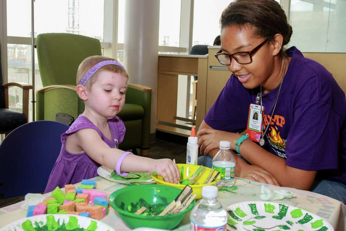 Caitlin Czagas, 2, volunteer Alexandria Gordon doing Snake Painting at Camp Periwinkle Days. Camp Periwinkle Days transforms the Texas Children's Cancer and Hematology Centers waiting rooms into a two-day camp with games, prizes and activities.