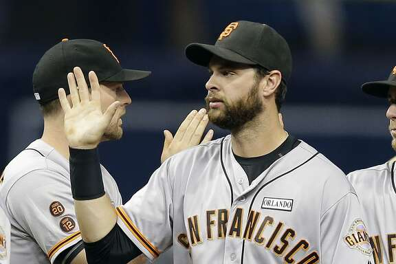 San Francisco Giants first baseman Brandon Belt shakes hands with teammates after the team defeated the Tampa Bay Rays in a baseball game Friday, June 17, 2016, in St. Petersburg, Fla. (AP Photo/Chris O'Meara)