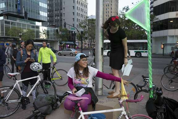 Charlotte Hryse, a bike party volunteer, motions to another volunteer at the starting point of May's East Bay Bike Party ride at Frank H. Ogawa Plaza in Oakland, Calif. on May 12, 2016.
