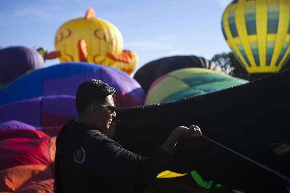 Alberto Rodriguez helps support Shadowdancer II as it begins the cold packing process during the Sonoma 26th Air Balloon Classic on Saturday, June 18, 2016 in Windsor, California.