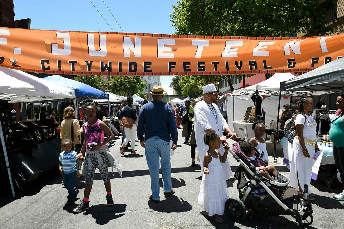 People walk under a banner during the Juneteenth Celebration in the Fillmore District of San Francisco, CA Saturday, June 18, 2016.