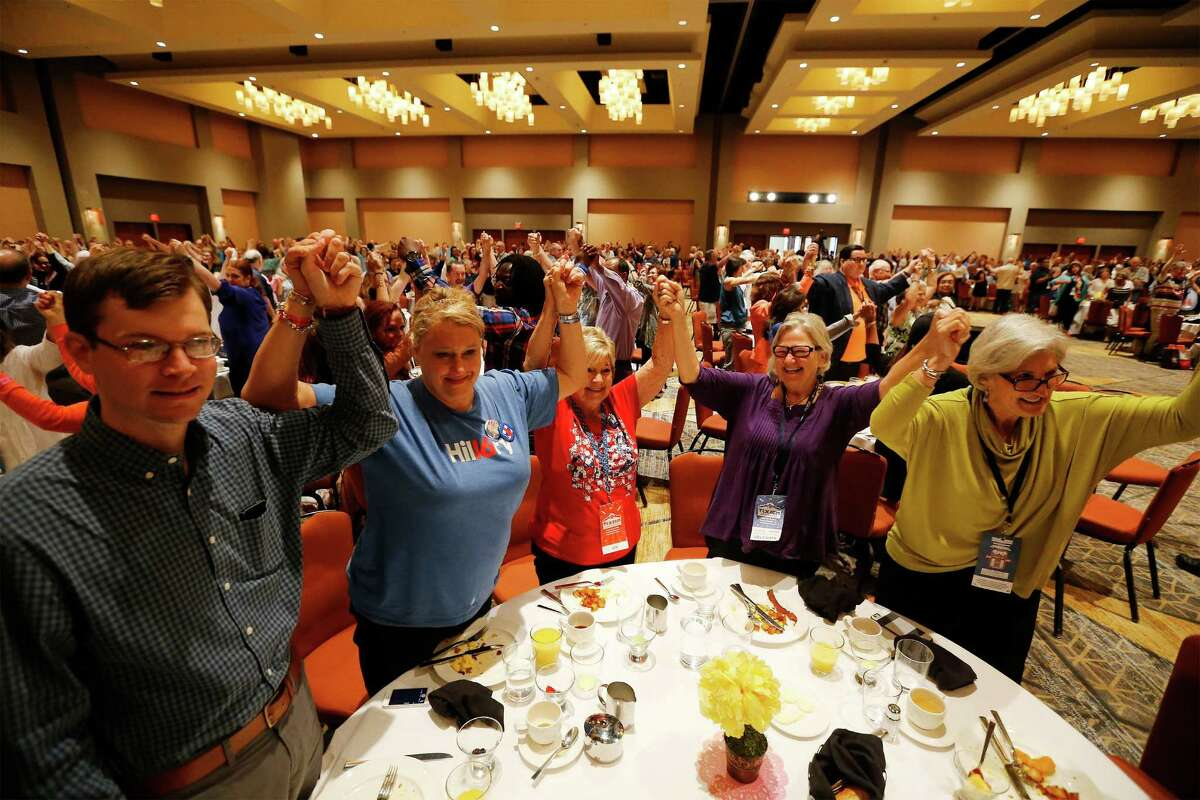 Texas Democrat delegates join hands as a sign of unity during the Lady Bird Johnson Breakfast at the Grand Hyatt during the final day of the Texas Democratic Convention on Saturday, June 18, 2016. (Kin Man Hui/San Antonio Express-News)