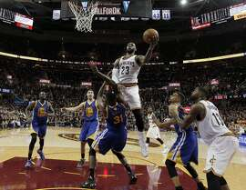 LeBron James (23) puts up a shot over Festus Ezeli (31) in the second half as the Golden State Warriors played the Cleveland Cavaliers in Game 6 of the NBA Finals at Quicken Loans Arena in Cleveland, Ohio, on Thursday, June 16, 2016.