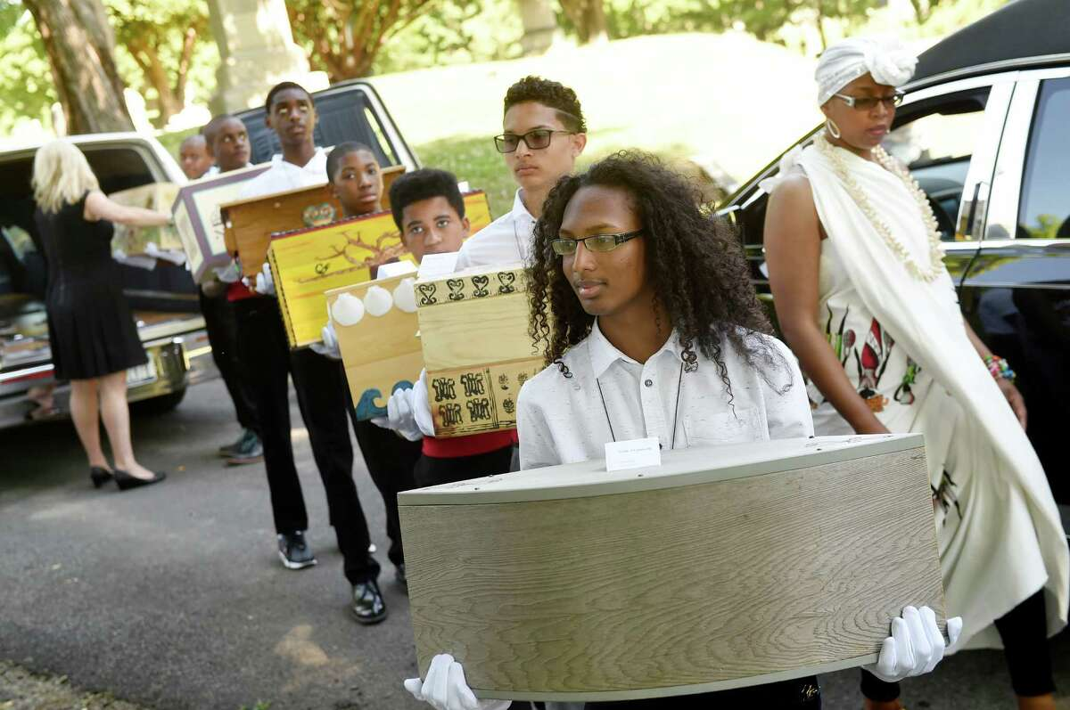 Shaune-Anthony Sundown, center, joins other pallbearers as they carry ossuaries containing the remains of 14 people enslaved in life during the Schuyler Flatts Burial Ground Project service on Saturday, June 18, 2016, at St. Agnes Cemetery in Menands, N.Y. (Cindy Schultz / Times Union)