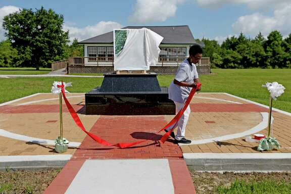 Curator Kathryn Ford sets up Friday for a ribbon cutting in Kendleton to welcome residents to the Fort Bend County Heritage Unlimited Museum's new Moore-Taylor Education Building, background, on the cusp of Juneteenth.