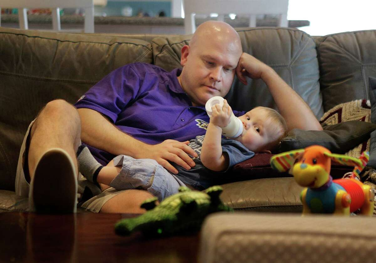 Jay Becraft, 43, a stay-at-home dad in Garden Oaks, gives his son, Jay Jr., a bottle before putting him down for a nap. He also cares for a 2-year-old daughter, Molly.