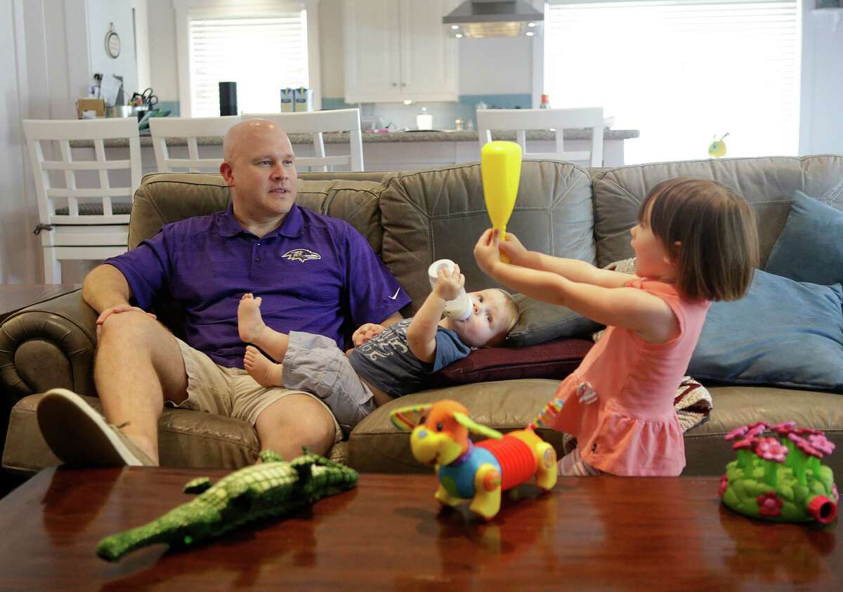 Jay Becraft, a stay-at-home dad, gives his son, Jay, Jr., a bottle while talking with his daughter, Molly, 2, at home, Tuesday, June 7, 2016, in Houston.