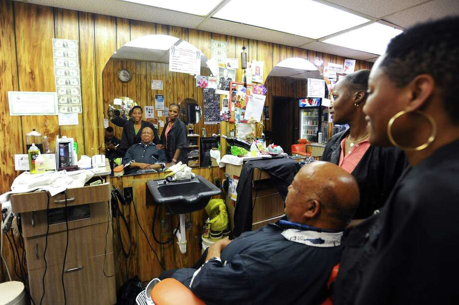 Thomas Bradford, owner of Superior Barbershop, poses with his daughter Thomasina Bradford, right, and Nicki Dorsey on Thursday, June 16, 2016. Photo: Michael Cummo / Hearst Connecticut Media / Stamford Advocate