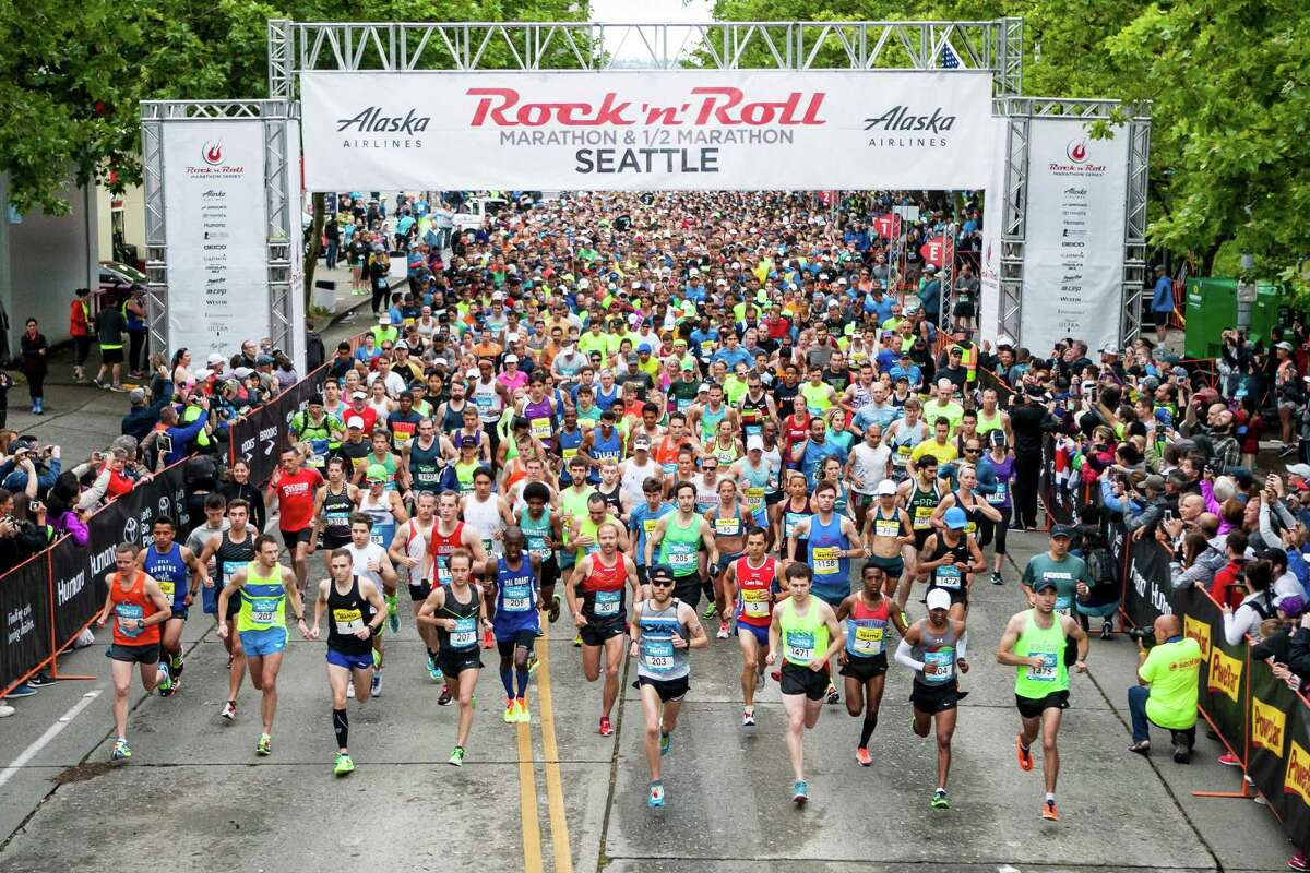 The first wave of marathon runners run through the starting gate at the Rock 'n' Roll Marathon in downtown Seattle on June 18, 2016.