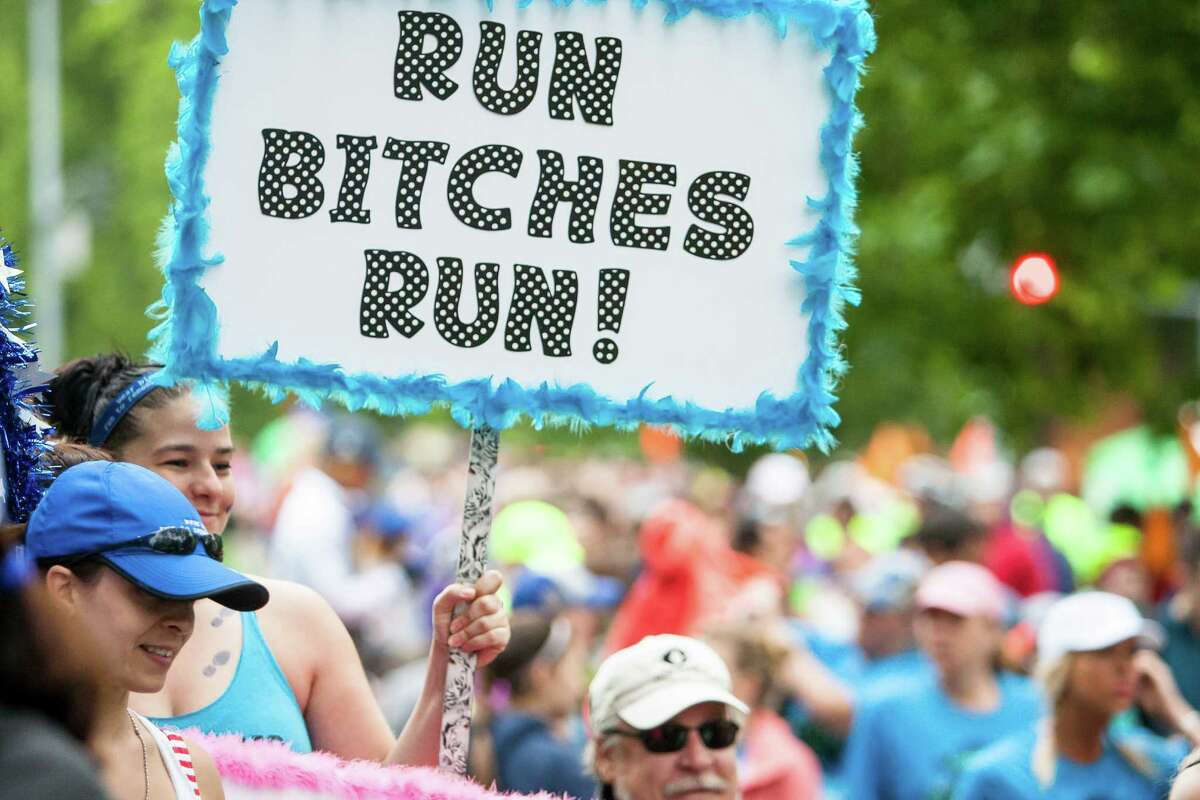 A spectator holds up a sign of encouragement at the starting line.