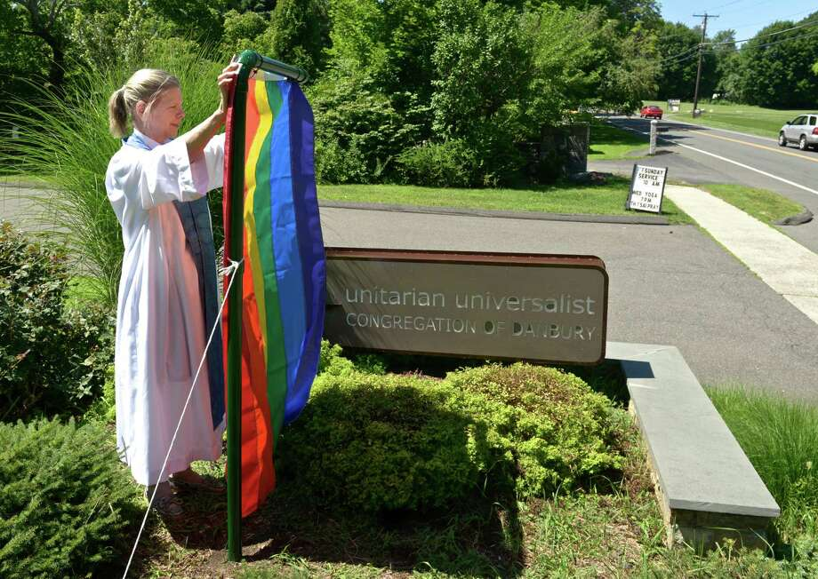 File photo of Rev. Barbara Fast Minister of the Unitarian Universalist Congregation of Danbury holds a replacement rainbow flag for one that was burned. The church is one of three organizations hosting a vigil Tuesday in honor of those killed at the nightclub shooting in Orlando. Friday, July 31, 2015, in Danbury, Conn. Photo: H John Voorhees III / Hearst Connecticut Media / The News-Times