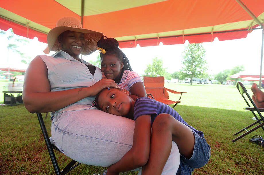 Charlene Phillips jokes with daughters Lea Phillips, 5, and L'Ashya Phillips, 9, as they snuggle with her and spend time with family during the City of Beaumont's annual Juneteenth celebration Saturday in Tyrrell Park. The event featured music, food, entertainment, and children's games as well as the opportunity for family and friends to gather for picnics and celebration to mark the official end of slavery in the United States.  Photo taken Saturday, June 18, 2016 Kim Brent/The Enterprise Photo: Kim Brent / Beaumont Enterprise