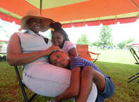 Charlene Phillips jokes with daughters Lea Phillips, 5, and L'Ashya Phillips, 9, as they snuggle with her and spend time with family during the City of Beaumont's annual Juneteenth celebration Saturday in Tyrrell Park. The event featured music, food, entertainment, and children's games as well as the opportunity for family and friends to gather for picnics and celebration to mark the official end of slavery in the United States.  Photo taken Saturday, June 18, 2016 Kim Brent/The Enterprise