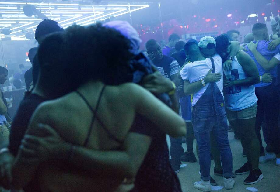 Club goers embrace at the approximate time one week ago that the Pulse nightclub mass shooting began as the music is turned off on the dance floor to observe a moment of silence at Parliament House, an LGBT nightclub early Sunday, June 19, 2016, in Orlando, Fla. (AP Photo/David Goldman) Photo: David Goldman/AP