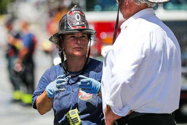 A firefighter talks to battalion chief Jack Cremen (right) after working inside the scene of a fire, the day after it destroyed a building near the corner of Mission St. and 29th St in San Francisco, California, on Sunday, June 19, 2016.