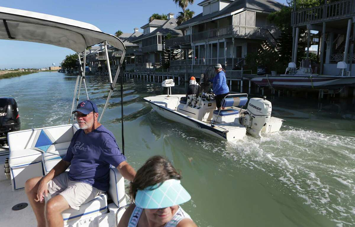 Garry Stebbins (left) and Maria Galasso pass another boat going out on a fishing trip at the Long Island Village which is near the proposed liquified natural gas plant in Port Isabel, Thursday, June, 9, 2016.