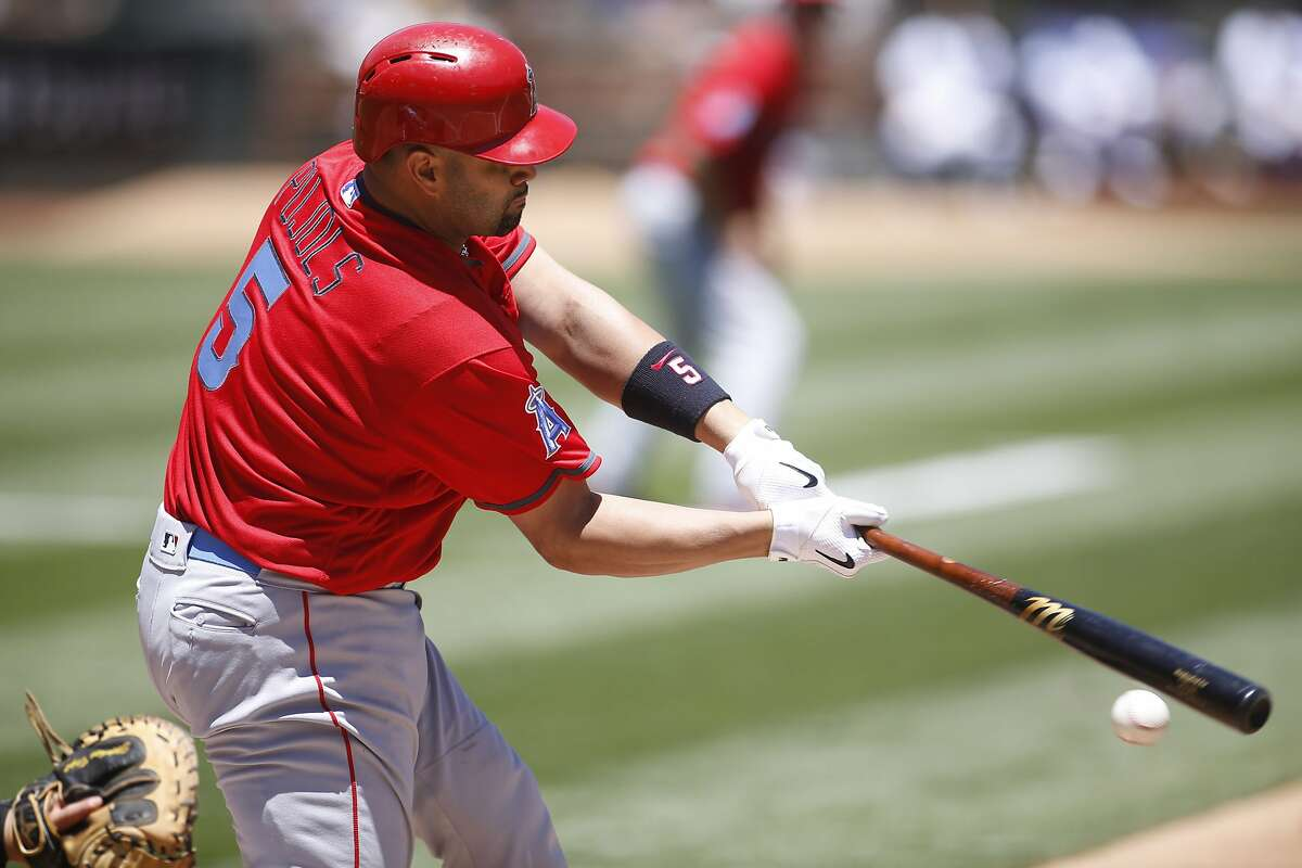 Los Angeles Angels' Albert Pujols hits an RBI-groundout against the Oakland Athletics during the first inning of a baseball game Sunday, June 19, 2016, in Oakland, Calif. Yunel Escobar scored on the play. (AP Photo/D. Ross Cameron)