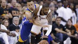 Golden State Warriors guard Stephen Curry (30) reaches against Cleveland Cavaliers guard Kyrie Irving (2) during the first half of Game 6 of basketball's NBA Finals in Cleveland, Thursday, June 16, 2016. (AP Photo/Tony Dejak)