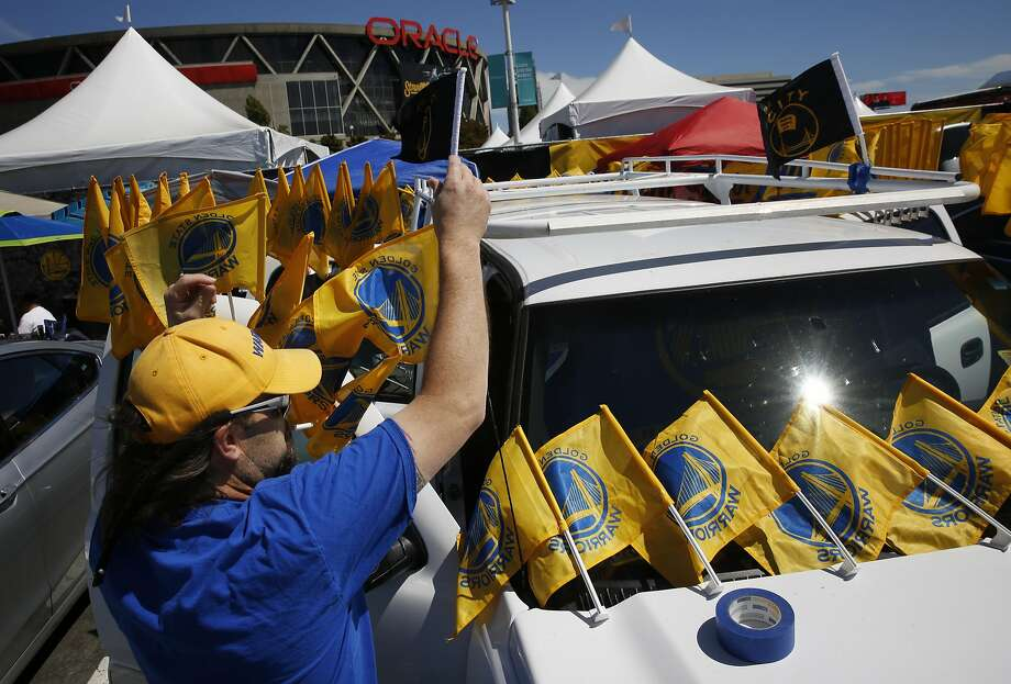 Tim Balazs attaches team flags onto friend Tom Clark's car before Game 7 of the NBA Finals featuring the Warriors and the Cavaliers at the Oracle Arena June 19, 2016 in Oakland, Calif. Photo: Leah Millis, The Chronicle