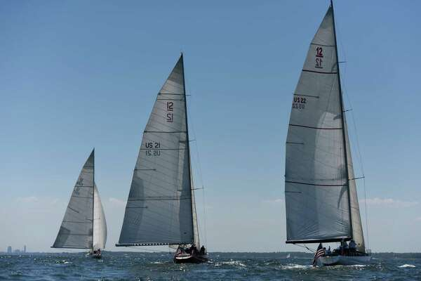 The Bank of America sailboat manned by disabled veterans, center, competes with two Bridgewater Associates boats in the Sail to Prevail Belle Haven Challenge Cup in the waters of the Long Island Sound off the shore of Belle Haven Club in Greenwich, Conn. Sunday, June 19, 2016. Twelve disabled veterans from New York and Connecticut served as active crew members on one of the three vintage America's Cup yachts that participated in the competitive sailing races on the Sound. Now in its 18th year, the Challenge Cup allowed the disabled vets to join in competitive camaraderie with Bank of America employees on their boat while competing against two Bridgewater Associates boats.