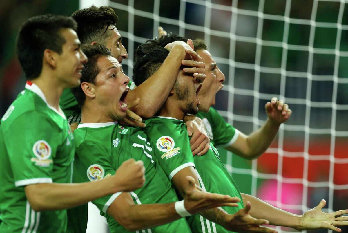 Mexico midfielder Hirving Lozano, left, forward Javier Hernandez (14) and Mexico forward Jesus Manuel Corona (10) celebrate Corona's game-tying goal against Venezuela during the second half of a Copa America Centenario group C soccer match on Monday, June 13, 2016, in Houston. The match ened in a 1-1 draw.