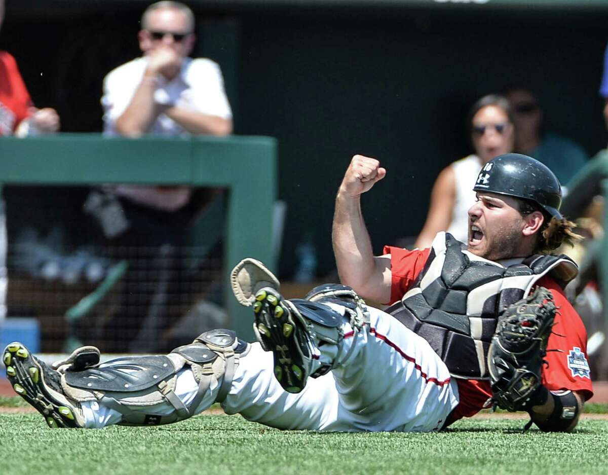 Texas Tech catcher Tyler Floyd pumps his fist after throwing out TCU Michael Landestoy to get out of a bases-loaded situation during the second inning of an NCAA men's College World Series baseball game in Omaha, Neb., Sunday, June 19, 2016. (AP Photo/Mike Theiler)