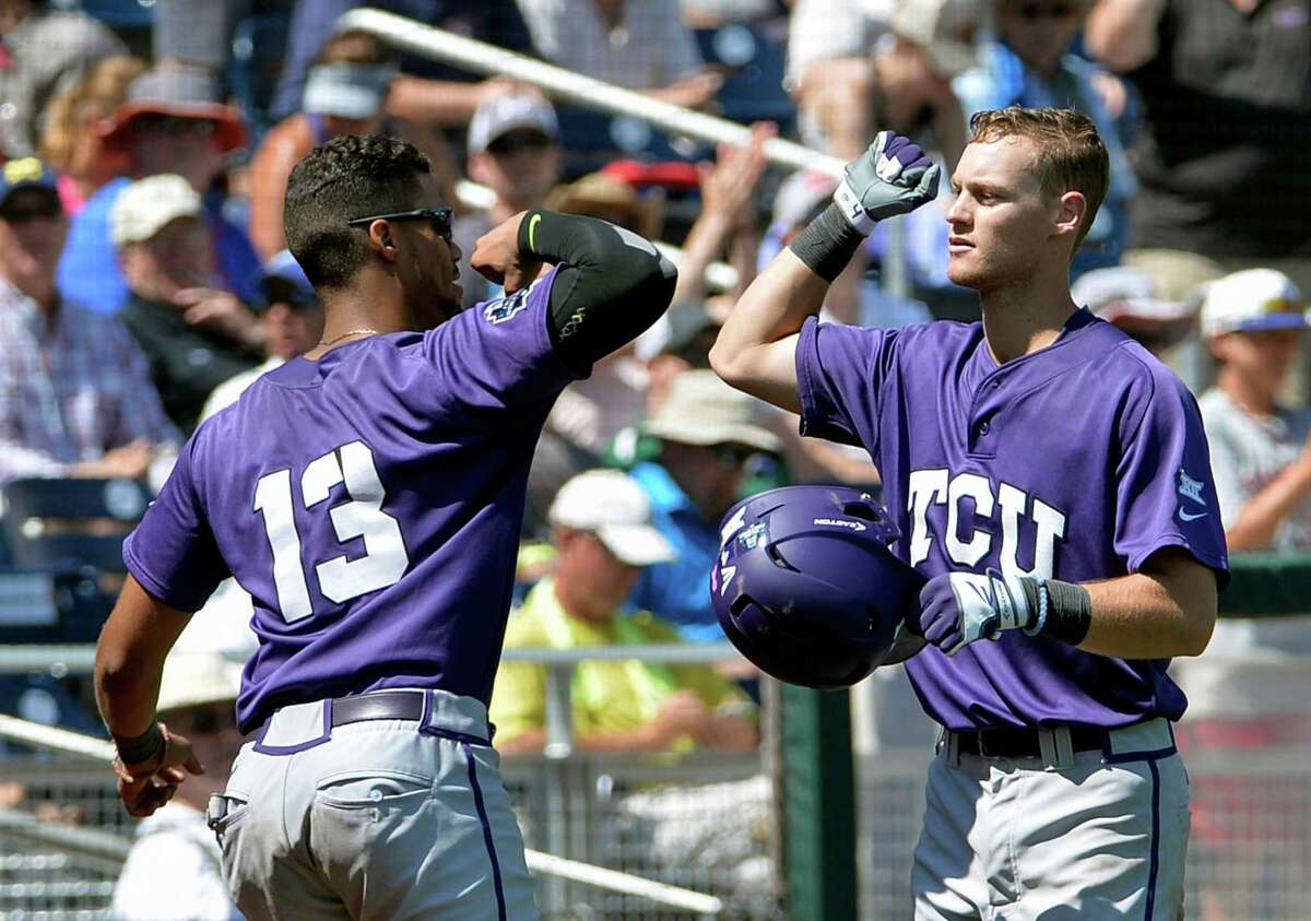 TCU Cam Warner, right, is congratulated by teammate Michael Landestoy (13) after scoring a solo home run during the fifth inning of an NCAA men's College World Series baseball game against Texas Tech in Omaha, Neb., Sunday, June 19, 2016. (AP Photo/Mike Theiler)