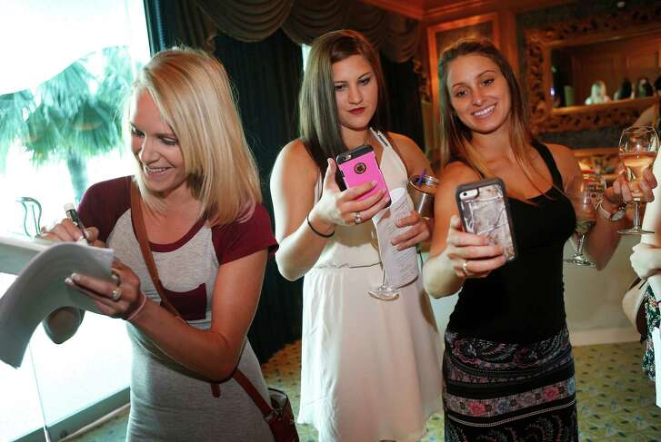 Kelsey Powell, right, and her friend Molly Dougherty, center, use Facebook Live from their phones while waiting in line to have their photo taken as part of an audition for the Bachelor series at the Downtown Aquarium.  in Houston, Thursday, June 16, 2016. ( Mark Mulligan / Houston Chronicle )