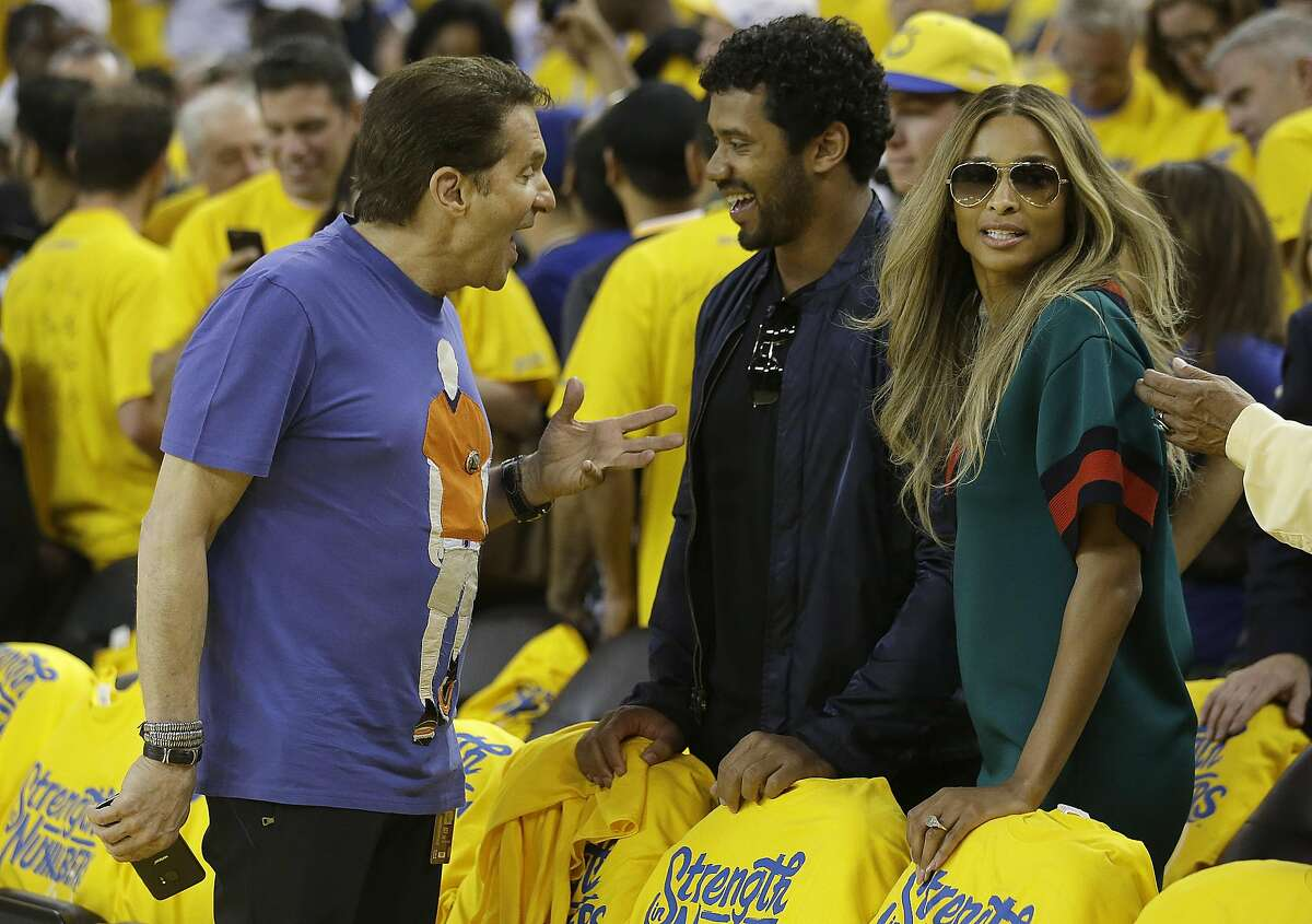 Golden State Warriors co-owner Peter Guber, left, talks with Seattle Seahawks quarterback Russell Wilson and Ciara before Game 7.