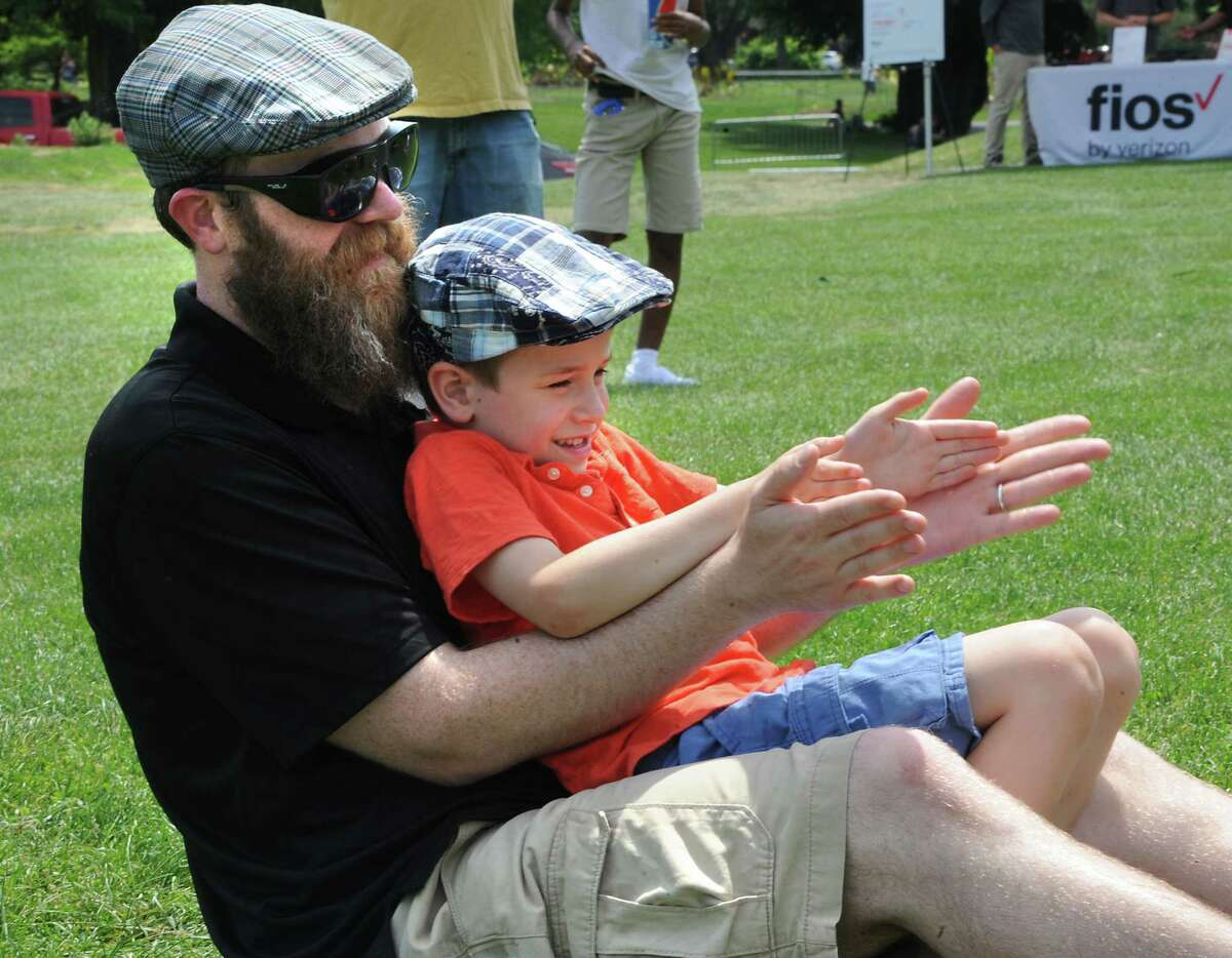 Mark Fiske of Downingtown, P.A. claps to the music of the Bondville Boys with his son Gavin, 6, during Dad Fest in Washington Park on Sunday, June 19, 2016 in Albany, N.Y. (Lori Van Buren / Times Union)