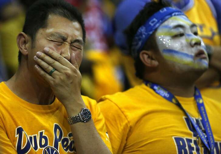 Warriors fans react after the Warriors lost to the Cavaliers in game 7 of the NBA Finals at the Oracle Arena June 19, 2016 in Oakland, Calif.