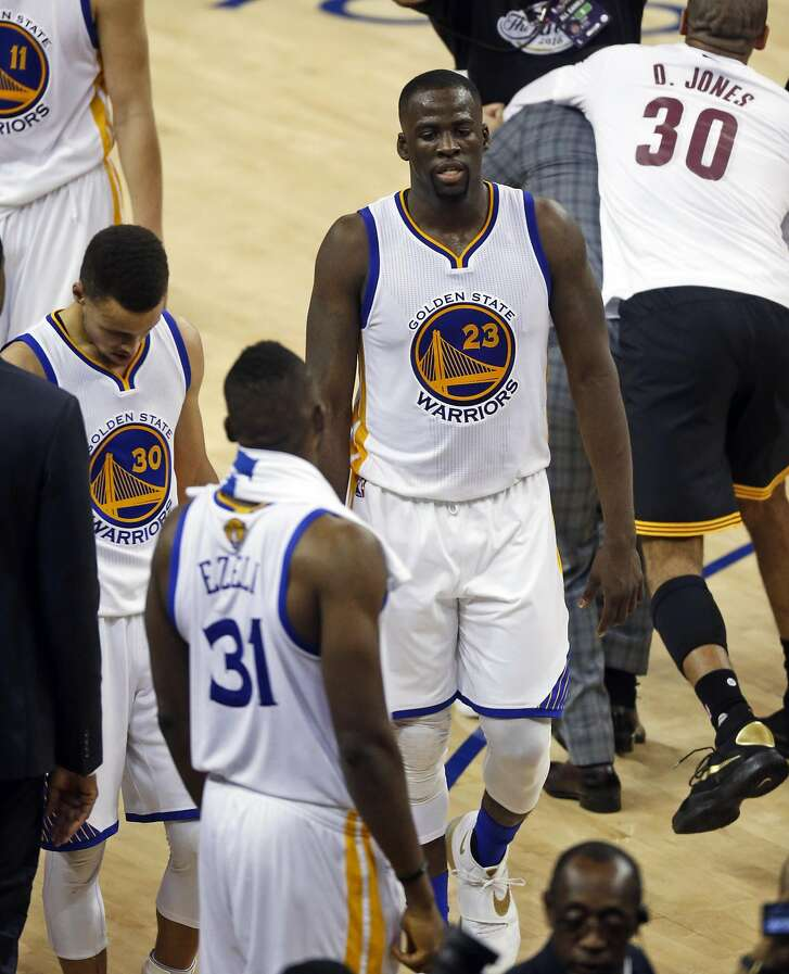 Golden State Warriors' Draymond Green and Stephen Curry walk off the court after 93-89 loss to Cleveland Cavaliers in Game 7 of the NBA Finals at Oracle Arena in Oakland, Calif., on Sunday, June 19, 2016.