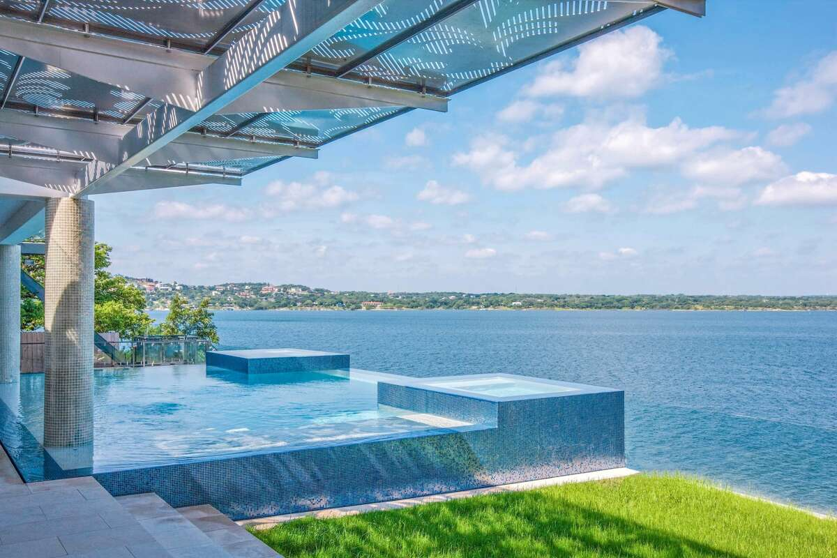 A negative-edge pool with two hot tubs overlook the lake.