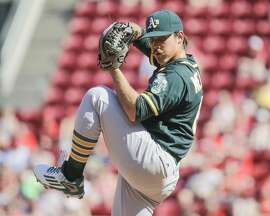 Oakland Athletics starting pitcher Daniel Mengden throws in the third inning of baseball game against the Cincinnati Reds, Saturday, June 11, 2016, in Cincinnati. The Reds won 2-1. (AP Photo/John Minchillo)