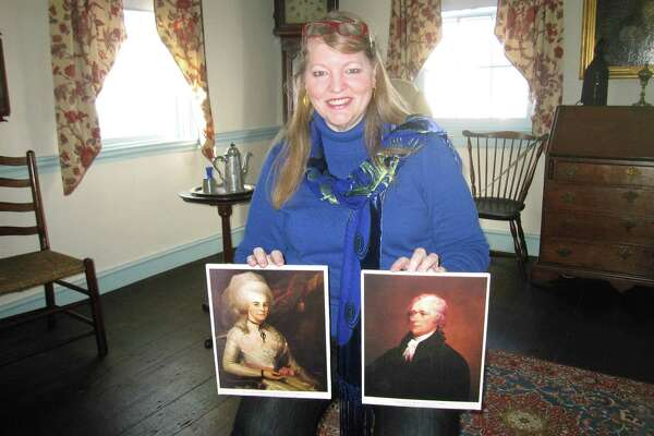 "This Jan. 20, 2015 file photo taken in the Schuyler-Hamilton House in Morristown, N.J., shows curator Patricia Sanftner holding pictures of Alexander Hamilton and his wife, Elizabeth Schuyler. Hamilton, who was George Washington's aide de camp, courted Schuyler at the house while troops were encamped at Morristown in 1779 and 1780 during the Revolutionary War. The house, also known as the Jabez Campfield House, is owned by the Daughters of the American Revolution. Interest in historic sites associated with Hamilton has increased thanks to the hit Broadway musical ""Hamilton."" (AP Photo/Beth J. Harpaz, File)"