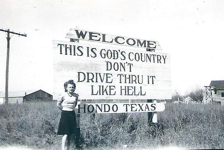 "Hondo's original ""This is God's Country, Don't Drive Thru It Like Hell"" sign is seen in this 1944 photo. / Released to Creative Commons by Wikipedia user ""Schrandtmatt"""