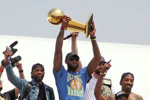 Cleveland Cavaliers' LeBron James holds up the NBA Championship trophy alongside teammates on JUne 20, 2016 after arriving in Cleveland, Ohio. Joining James are Kyrie Irving, left, Kevin Love, J.R. Smith and Tristan Thompson as they arrive at Atlantic Aviation.