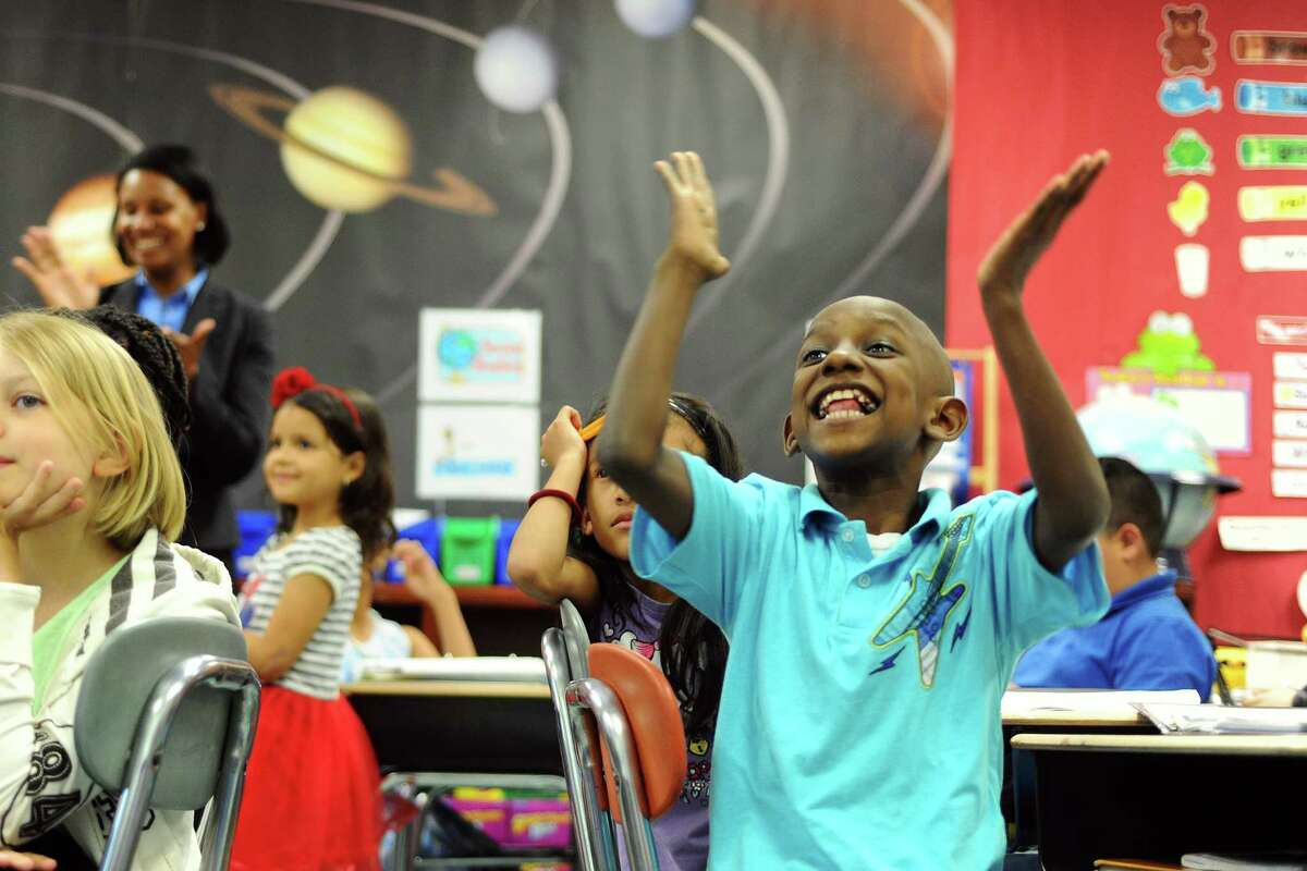 Dave Derose, 8, cheers loudly after Stamford interim superintendent James Connelly said hello and thank you properly in French Creole inside the English Language Learners program at Davenport Elementary School.