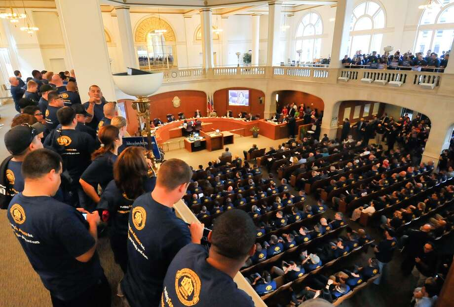 Members of the police and firefighters unions fill the City Council Chamber during a meeting to approve the FY2015 budget. The police union has arrived at a contract with the city; firefighters have refused to negotiate. Photo: Robin Jerstad /For The Express-News / San Antonio Express-News
