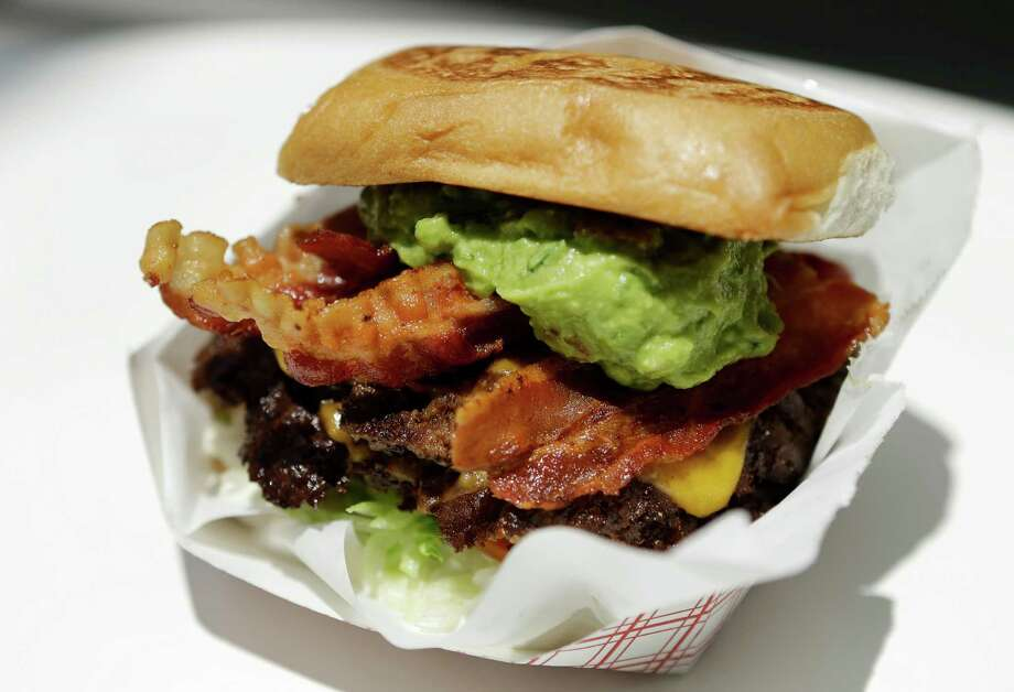 A double cheddar cheese burger with bacon and guacamole from Kuma Burgers in the food court at 3 Greeway Plaza. Photo: Melissa Phillip, Staff / © 2016 Houston Chronicle