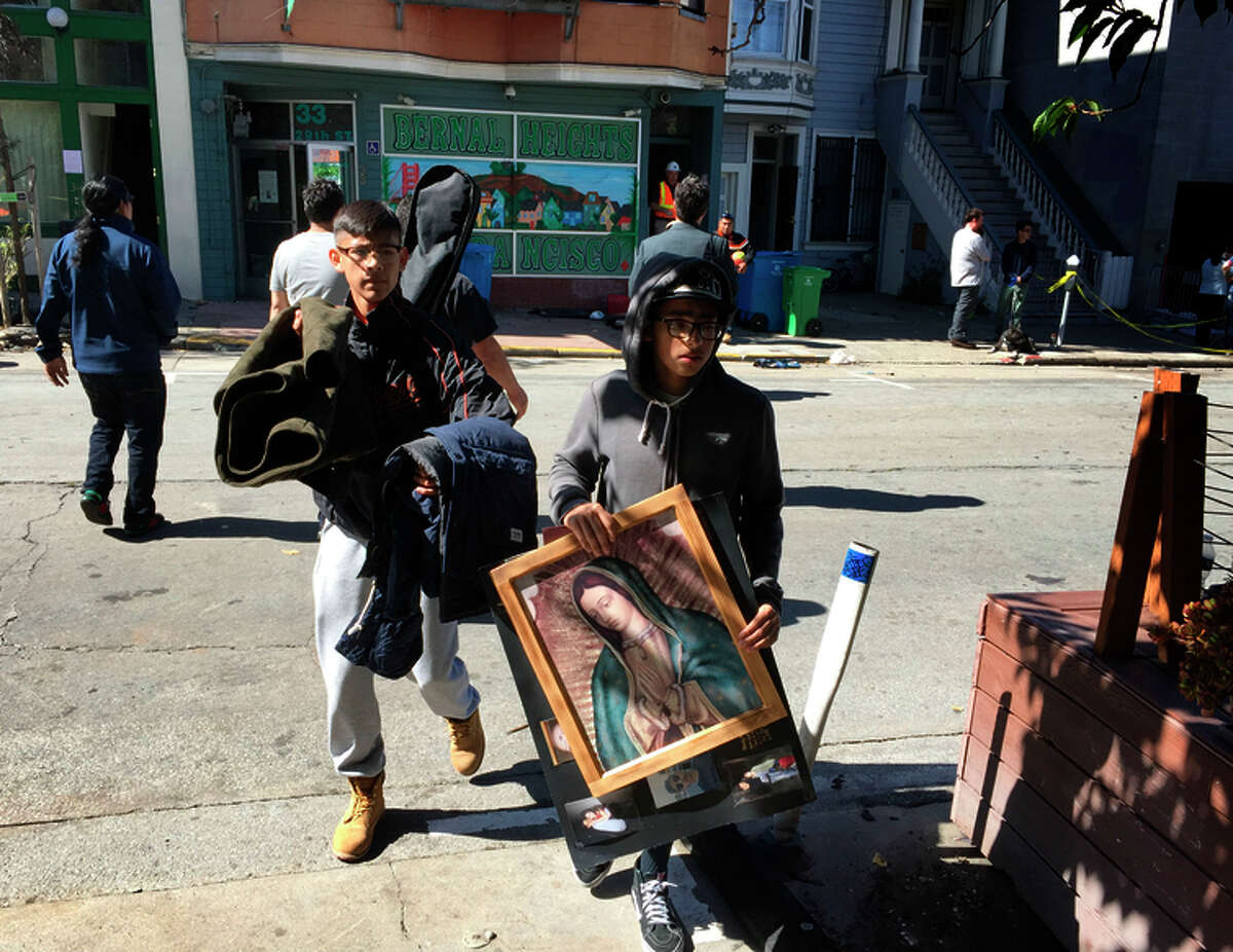 People displaced by Saturday's big fire in the Outer Mission collect their belongings.
